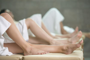 Detail shot of legs of young people, relaxing on laungers after sauna in health spa center. They are lying down on deck chairs and they have their eyes closed.
